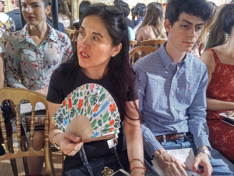 Paola Sandoval, presidenta de la Asociación de la Prensa Extranjera (APE) observa atentamente el paso de las modelos mientras se abanica.