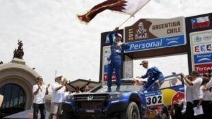 Пилот из Катара Насер Аль-Аттия (Фольксваген) празднует свою победу в классе легковых автомобилей в ралли Дакар 16 января 2011 года