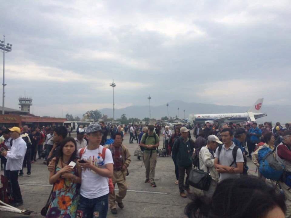 Pessoas aguardam na pista do aeroporto de Katmandu, capital do Nepal, para evitar se aproximar de desmoronamentos.