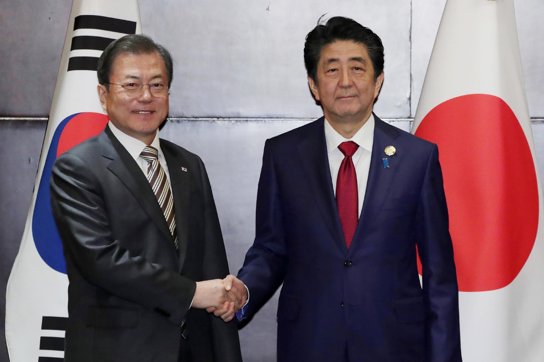 O Primeiro-ministro do Japão Shinzo Abe (à direita) e o Presidente da Coreia do Sul, Moon Jae-in (à  esquerda).