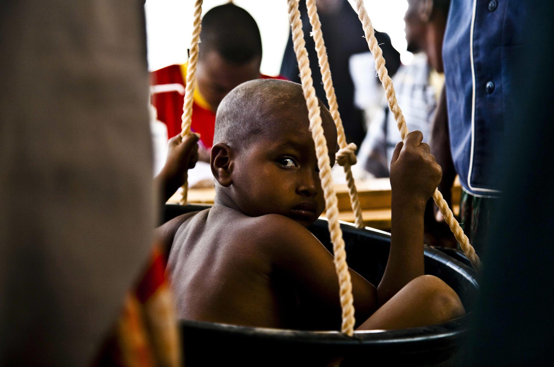 Ребенок только что прибывших сомалийских беженцев проходит медицинский осмотр в беженском лагере Дагааб в Кении 23 июля 2011 года