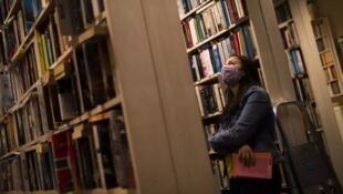 Mulher olha as prateleiras de uma livraria em Bruxelas, 11 de junho de 2020.