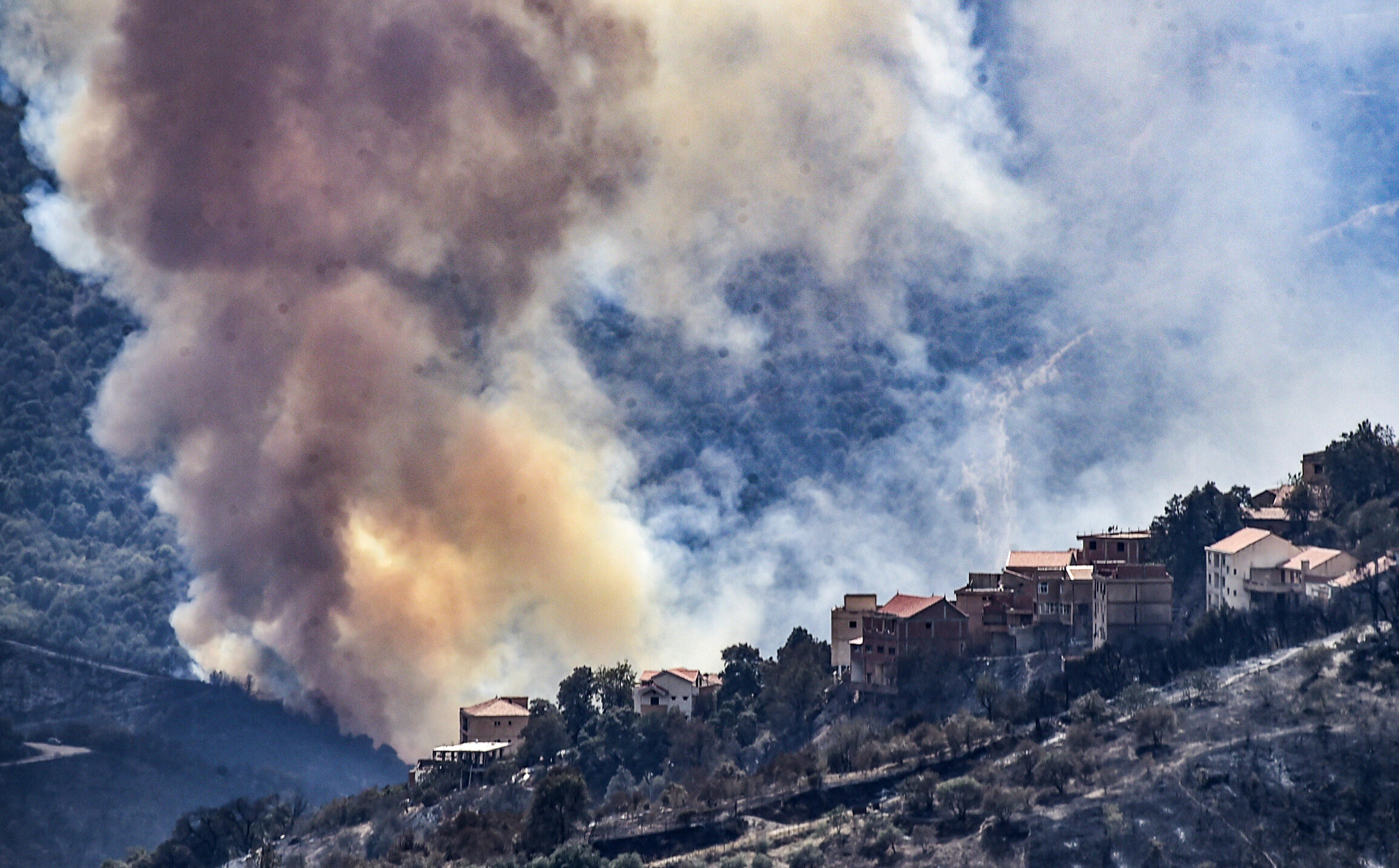 Heavy smoke rises during a wildfire in the forested hills of the Kabylie region, east of the Algerian capital Algiers