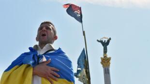 Un homme enroulé dans un drapeau ukrainien chante l'hymne national sur Maïdan à Kiev. 8 juin 2014.