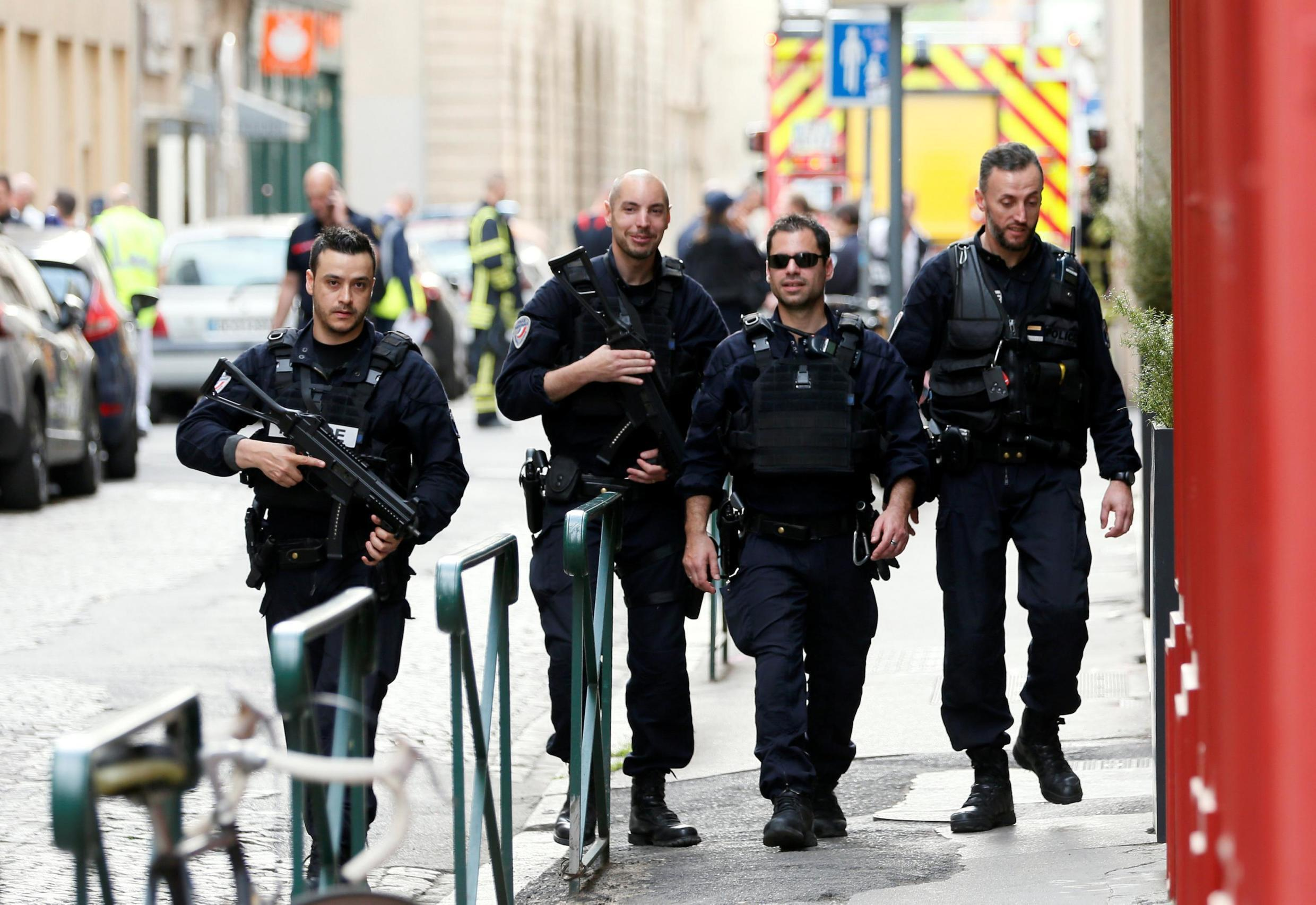 Police officers searching the area around the site of Friday's bomb attack in Lyon.