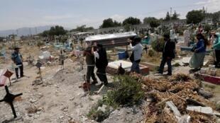 Une famille enterre le corps d'une femme décédée du coronavirus dans la banlieue de Mexico le 19 juin 2020.