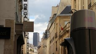 The narrow Rue des Saints-Pères on the Left Bank of Paris, with the Tour Montparnasse skyscraper in the background.