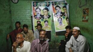 Un grupo ve las noticias en televisión en una casa de té tradicional, decorada con carteles electorales, en la vieja ciudad de Lahore, el 10 de mayo de 2013.