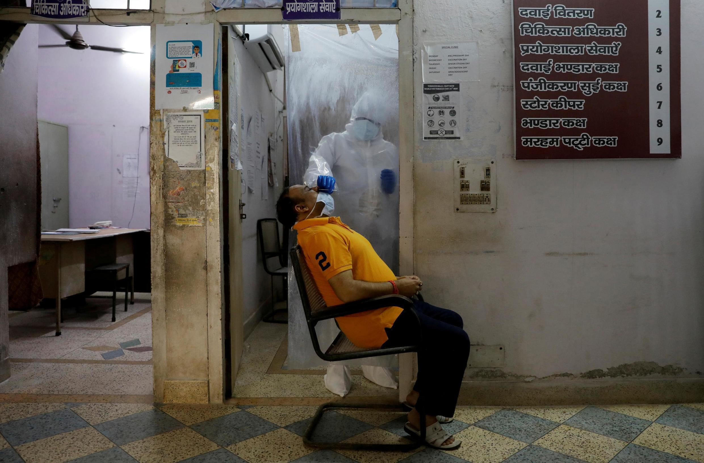 Trabalhadores da saúde colhem amostras para testar um homem para o Covid-19 em Nova Délhi, em 27 de junho de 2020.
