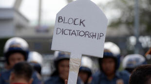 """A protester displays an anti-Marcos slogan during a protest in front of the heroes' cemetery in Manila on February 25, 2017, to coincide with the anniversary of the """"People Power"""" revolution."""