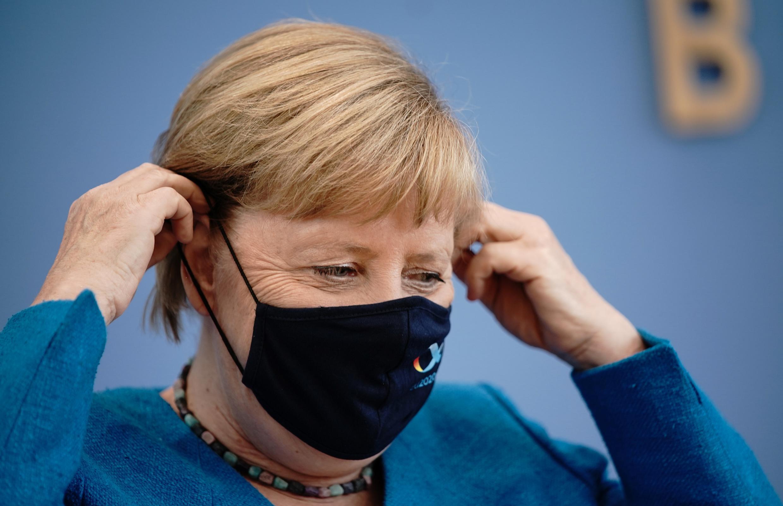 La canciller alemana, Angela Merkel, se pone una mascarilla antes de partir después de su conferencia de prensa anual de verano, el 28 de agosto de 2020, en Berlín.