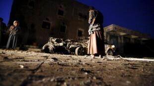 Mtu anayebebelea silaha akitazama moja ya magari yaliyolipuka katika mji mkuu wa Yemen, Sanaa, Jumatano Juni 17.