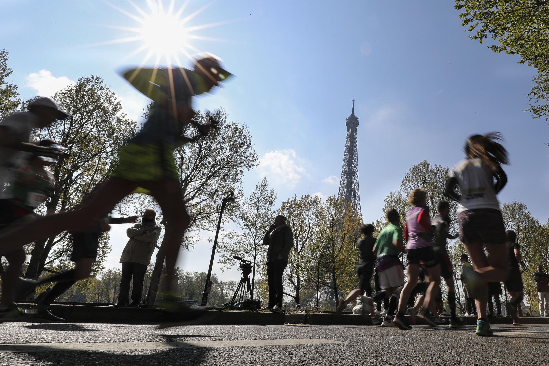 Des participants au marathon de Paris passent devant la Tour Eiffel, le 14 avril 2019 à Paris