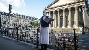 Many Paris cafes and restaurants now claim more space on the street to maximise outdoor dining