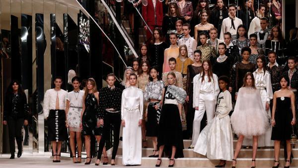 Final do desfile Métiers d'art da Chanel, com Virginie Viard à esquerda. Cenário reproduz escadaria espelhada da loja da marca em Paris.