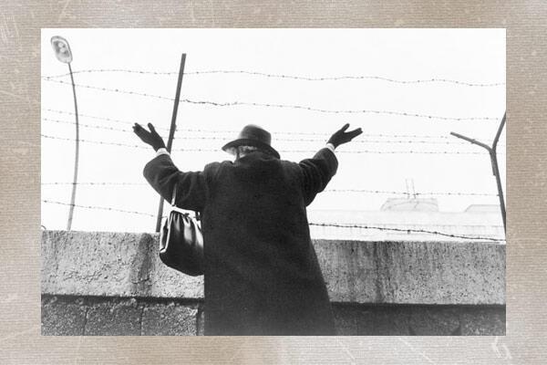 Femme faisant un signe devant le Mur de Berlin.