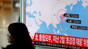 A woman walks past a television broadcasting a news report on North Korea firing ballistic missiles, at a railway station in Seo