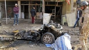 Soldado observa carcaça de carro-bomba que explodiu na mahã desta quinta-feira em Bagdá.