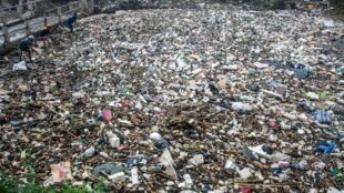 des villageois recherchent des déchets recyclables sur des ordures flottantes couvrant la rivière Citarum à Bandung, en Indonésie. (Image d'illustration)