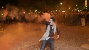 Um manifestante mascarado enfrenta a polícia francesa perto da torre Eiffel ao final de um protesto contra a legalização do casamento gay em Paris, nesta terça-feira, 23 de abril de 2013.