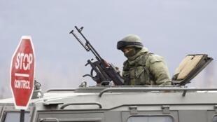 Homem armado controlando a entrada do aeroporto de Simferopol, neste 11 de Março de 2014.