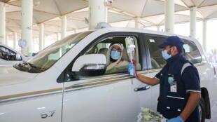Un douanier offre des fleurs aux passagers le premier jour de la réouverture des frontières entre le Qatar et l'Arabie saoudite, le 9 janvier 2021.