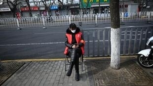 Un agent de sécurité portant un masque, assis sur une chaise le long d'une rue fermée en raison de l'épidémie de coronavirus à Pékin le 21 février 2020.