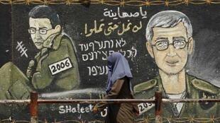 """Una palestina camina junto a un mural que representa a Shalit, en Gaza, el 23/06. En la leyenda en árabe puede leerse: """"Sionistas, no nos aburriremos hasta que ustedes se aburran"""". En hebreo: """"Sionistas, no nos cansaremos hasta que ustedes se cansen""""."""