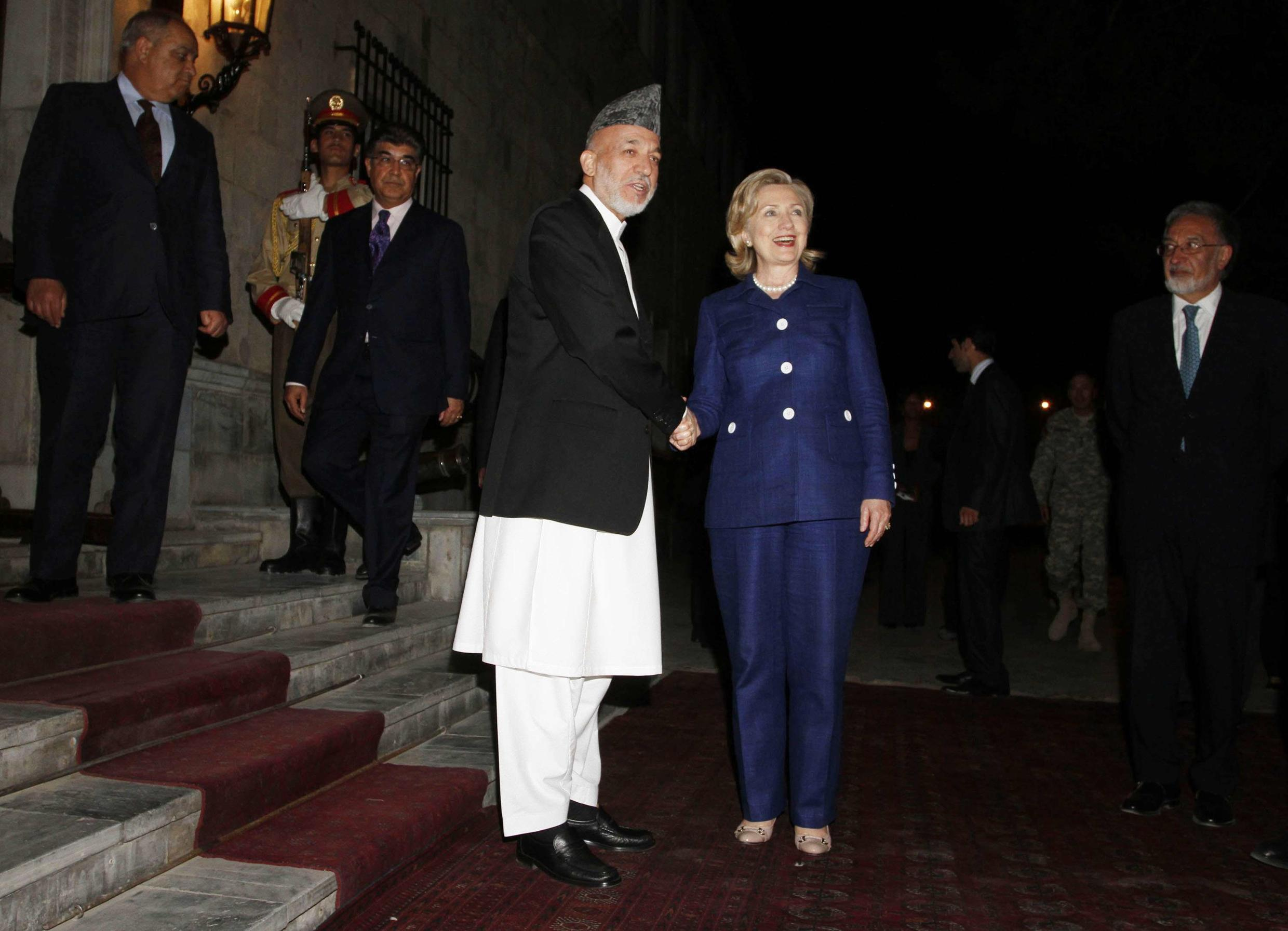Afghan President Hamid Karzai shakes hands with U.S. Secretary of State Hillary Clinton after her arrival at the presidential palace in Kabul
