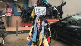 Modou Fall «l'homme plastique» lors de l'une de ses interventions au marché de Dakar (Sénégal) le 13 novembre 2019.