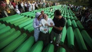Des Bosniaques musulmans devant les 613 cercueils prêts à être déposés au mémorial de Potocari, le 10 juillet 2011