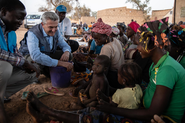 Filippo Grandi, le Haut Commissaire des Nations unies pour les réfugiés, s'entretient avec des femmes et des enfants dans un quartier qui accueille des personnes déplacées du nord du Burkina Faso à Kaya, le 2 février 2020.