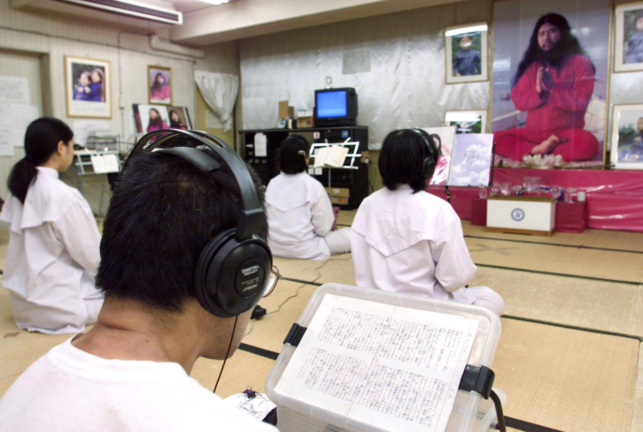 Seguidores da seita Aum diante de um retrato do guru Shoko Asahara em Tóquio, Japão, em 19 de julho de 1999.