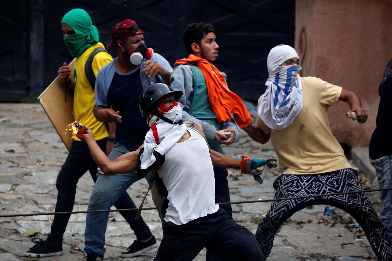 مخالفان نیکلا مادورو، رئیس جمهور ونزوئلا هنگام درگیری با پلیس این کشور، در جریان اعتصاب عمومی روز پنجشنبه ٢٩ تیر/ ٢٠ ژوئیه ٢٠۱٧