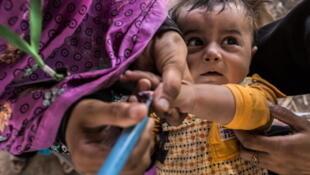 Un enfant dans les bras de sa mère pour être vacciné contre la poliomyélite à Jalozai, le 13 juillet 2012.