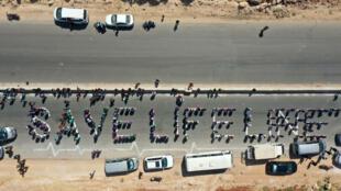 Una cadena humana formada por trabajadores de la sociedad civil pide mantener una resolución de la ONU que autorice el paso de ayuda humanitaria a la provincia noroccidental siria de Idlib, en el noroeste de Siria, a través del paso fronterizo de Bab al-Hawa con Turquía, el 2 de julio de 2021