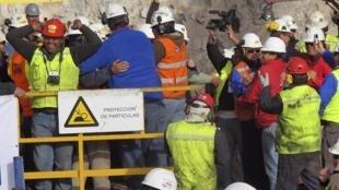 Работники буровой машины празднуют завершение бурения скважины, ведущей к 33 шахтерам, которые пробыли в забое два месяца