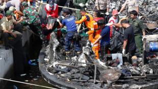 Policiais e membros da Cruz Vermelha retiram corpos de vítimas após incêndio a bordo de barco turístico indonésio, em 1° de janeiro de 2017.
