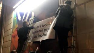 Manifestação da associação Attac na loja da Apple, na avenida Champs Elysées, em Paris.