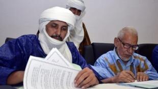 Le chef de la délégation d'Ansar Dine, Algabass Ag Intalla (G) et Ahmed Ould Sidi Mohamed du Mouvement arabe de l'Azawad cosignent le protocole d'accord.