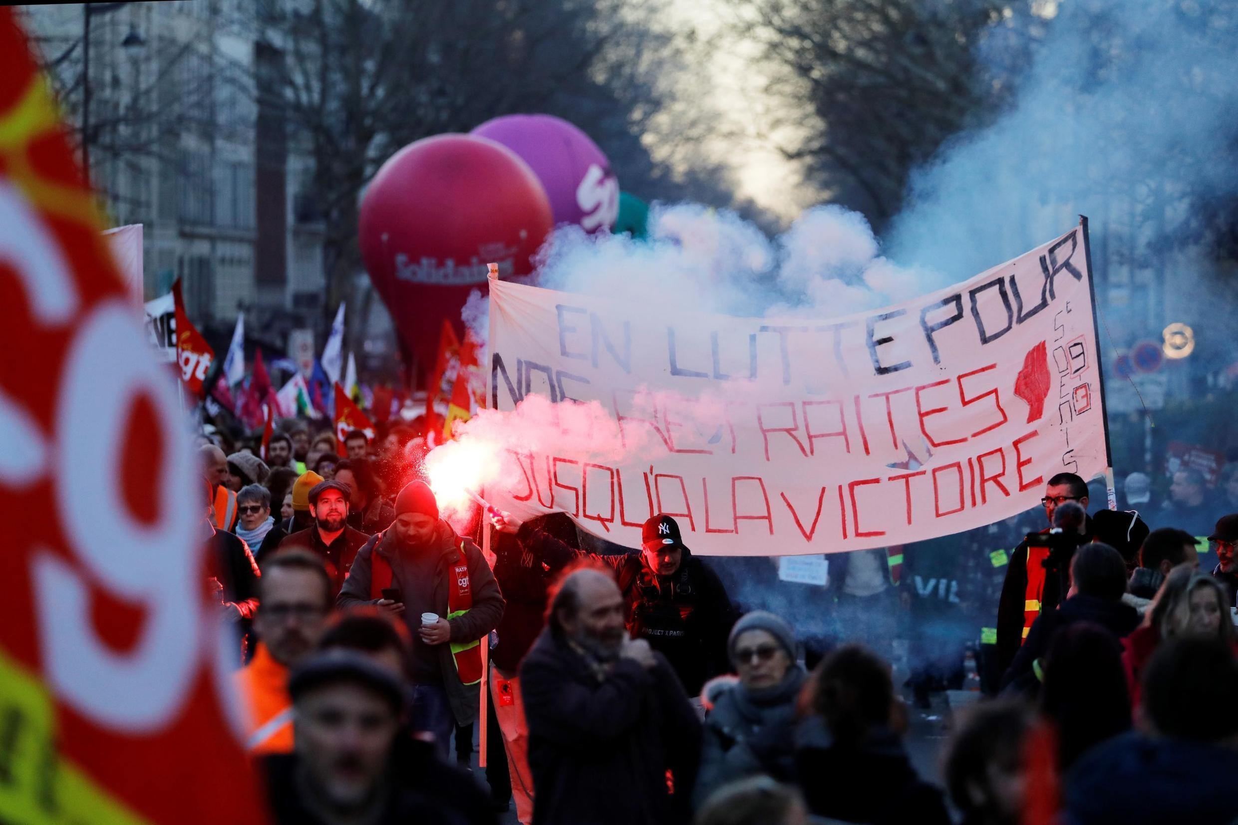 """Protesters hold a banner reading """"Fight for our retirements until victory"""" during a demonstration against the French government's plan to overhaul the country's retirement system in Paris, on February 6, 2020."""