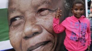 Criança sul-africana diante de foto de Nelson Mandela.