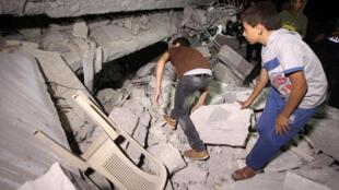Des Palestiniens inspectent ce qu'il reste de la maison de Hussam Qawasmeh, le 18 août 2014, désigné, dès la mi-juillet, comme le principal suspect dans la mort des jeunes Israéliens.