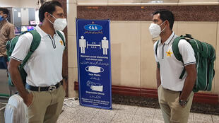 Pakistan cricketers Sarfaraz Ahmed (left) and Asad Shafiq donning facemasks at the Allama Iqbal International airport in Lahore on Sunday before leavng for England