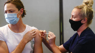 La nadadora australiana Cate Campbell (I), bicampeona olímpica, recibe la primera dosis de la vacuna contra el covid-19 en Queensland, Australia, el 10 de mayo de 2021