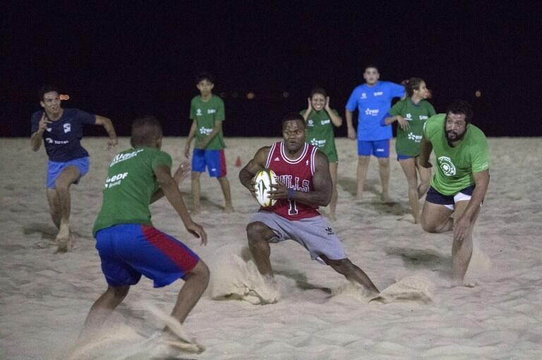Le Français de rugby à 7, Virimi Vakatawa (maillot rouge) joue avec une équipe locale de rugby, sur la plage de Copacabana à Rio de Janeir0  au Brésil , le 28 Juillet 2016.