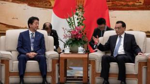 Shinzo Abe, primeiro-ministro japonês (à esquerda) e o seu homólogo chinês Li Keqiang, em Pequim a 25 de Outubro de 2018.