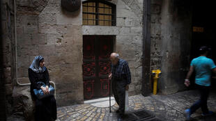 People pass by the seventh station of the cross on Via Dolorosa in Jerusalem's Old City