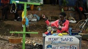 Une artiste fabrique et vend des masques dans le bidonville de Kibera, à Nairobi, le 14 avril 2020.