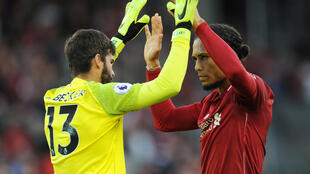 Liverpool's Virgil van Dijk celebrates with Alisson after the match